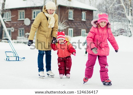 Mother with her daughters skates on ice skating in the winter.