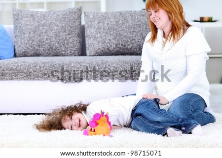mother with her happy  daughter, playing on floor at home