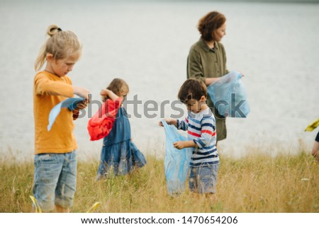 Mother with her kids collecting garbage on a meadow next to the river on a cloudy summer day. Environmental pollution. Ecological problem. #1470654206
