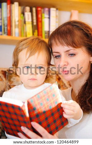 Mother with her little baby son reading book at home