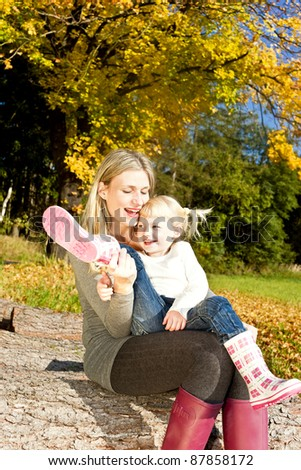 mother with her little daughter in autumnal nature