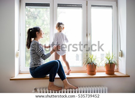 Mother with her little daughter looking out of window