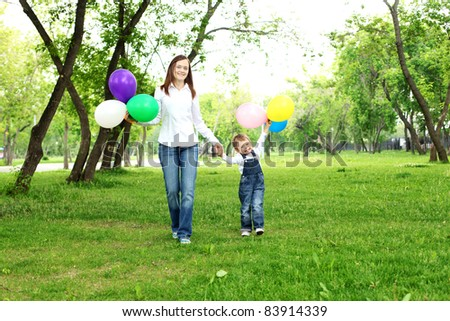 Mother with her son in the summer park with baloons