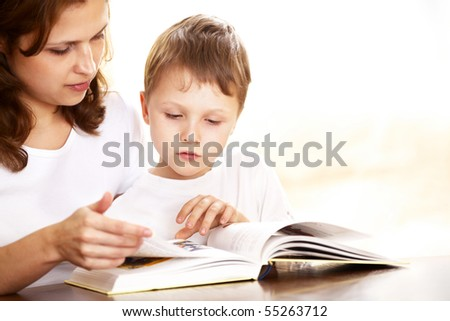 mother with her son reading indoor