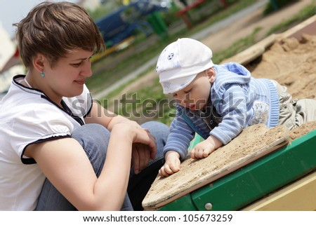 Mother with her toddler ate playing in sandbox in summer
