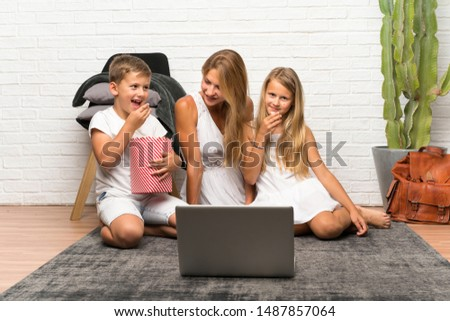 Mother with her two children at indoors and with popcorns