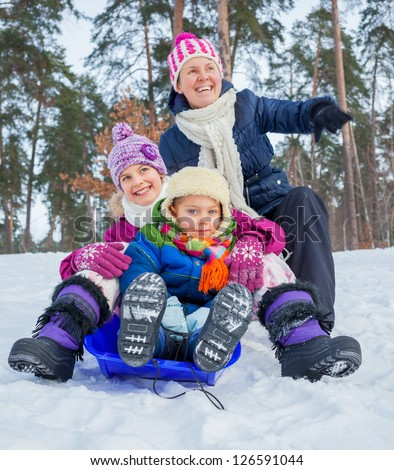 Mother with her two kids is sledging in winter-landscape. Focus on the boy.
