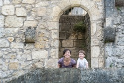Mother with her young son, both of them are smiling. They are crouched on a kerb of a staircase, this staircase takes you to the entrance of a park which you have to pass under a limestone arch.