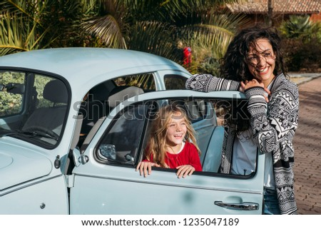 Mother with his daughter in the old car #1235047189