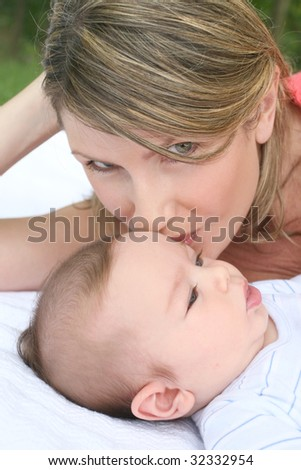 Mother with infant baby boy son, smiling and happy