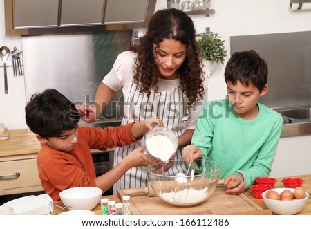 Mother with kids in the kitchen - stock photo