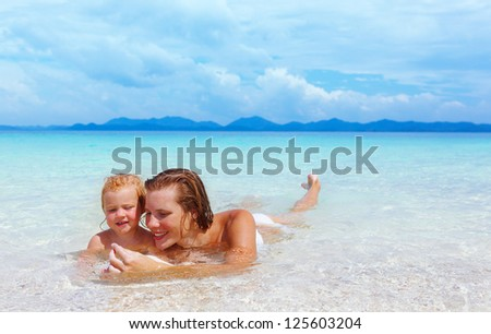 Mother with little baby girl on summer beach