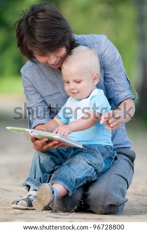 Mother with little son in the green park reading a book