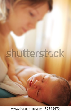 Mother with sleeping newborn baby daughter indoor. Close-up, shallow DOF.