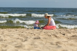 Mother with small baby girl relaxing on sea beach at sunny summer day.