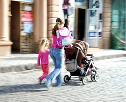 Mother with small child and a stroller walking down the street. Intentional motion blur