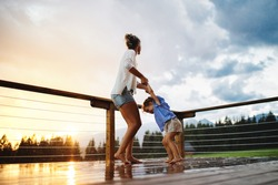 Mother with small daughter playing in rain on patio of wooden cabin, holiday in nature concept.