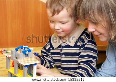 Mother with small son play with building set for children (built a house)