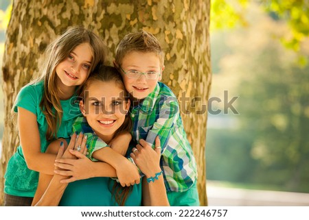 Mother with son and daughter on a walk in park in late summer afternoon