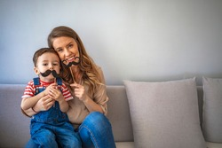 Mother with son holding photo booth mustache. Woman and kid on a grey background. Concept of celebration Father day. Playful mother and her son holding a fake mustache and playing