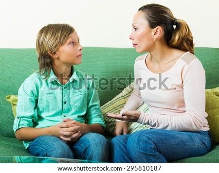 Mother with  teenager son having serious conversation in home
