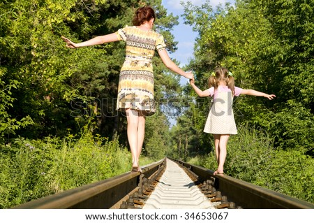 Mother with the daughter go on rails, a back to a camera, in a wood, in the summer, wood