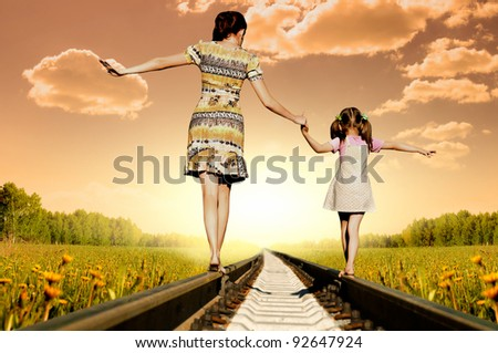 Mother with the daughter go on rails, a back to a camera, in field, in the summer