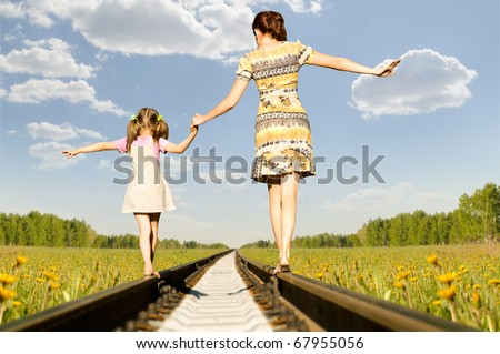 Mother with the daughter go on rails,  back to a camera, on nature, in the summer