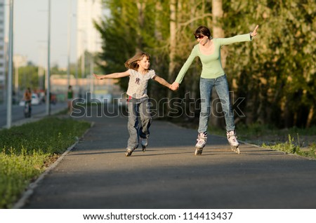 Mother with the daughter go on  roller skates, outdoor, in the evening summer