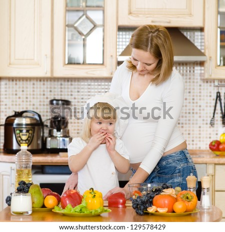 mother with the daughter make a dinner in kitchen