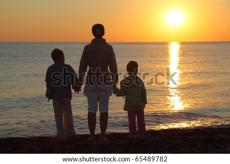 Mother with two children, embarking on hands stand on  beach  person to sea and look at sunset