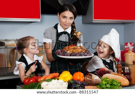 mother with two daughters in the kitchen preparing Christmas dinner with turkey and vegetables