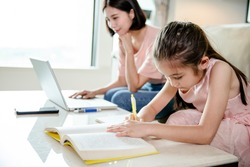 mother working at  home and help daughter doing home work