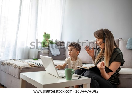 Mother working from home with kid. Children make noise and disturb woman at work. Homeschooling and freelance job. Moms Can Balance Work and Family. Multitasking mother working from home.