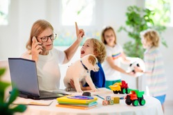 Mother working from home with kids. Homeschooling and home office.  Quarantine, closed school, coronavirus outbreak. Self isolation and social distancing. Children make noise and disturb mom at work.
