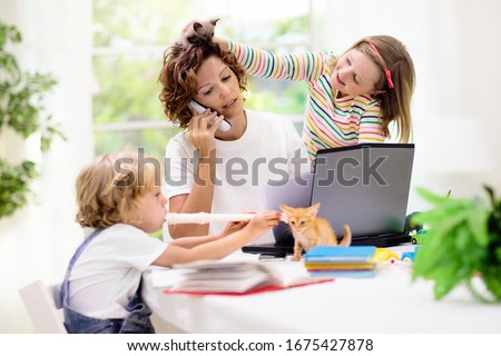Photo of  Mother working from home with kids. Quarantine and closed school during coronavirus outbreak. Children make noise and disturb woman at work. Homeschooling and freelance job. Boy and girl playing.