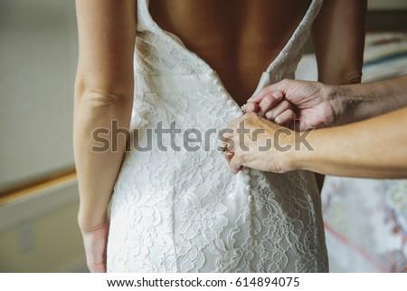 Mother Zipping Up Bride's Wedding Dress Foto stock ©