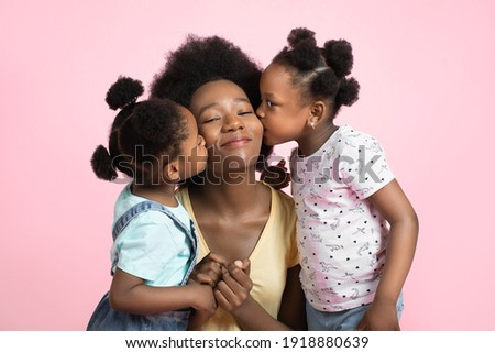 Motherhood and family concept. Lovely cute two little African girls kids in summer outfits, having fun and kissing their happy smiling young pretty mother, posing on isolated pink background