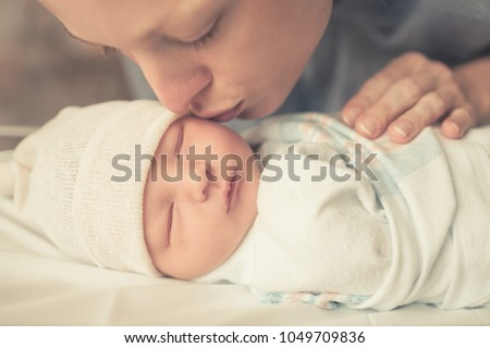 Motherhood, and parenting. Mother kissing her sleeping baby boy on cheek.