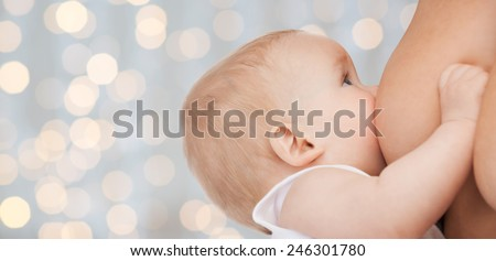 motherhood, children, people and care concept - close up of mother breast feeding adorable baby over holidays lights background