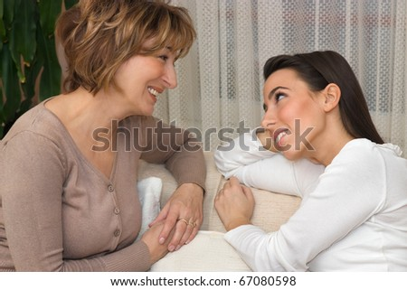 Motherr and her beautiful daughter friendly chatting in the living room.