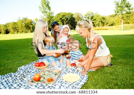 Mothers and kids having picnic in the backyard