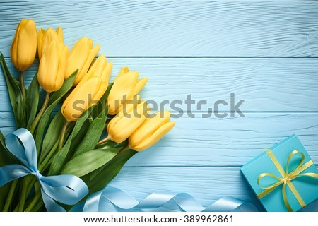 Mothers Day background. Tulips bouquet and gift box on blue wood. Beautiful spring pink and yellow flowers. Still life, top view, copy space. Unusual creative holiday greeting card