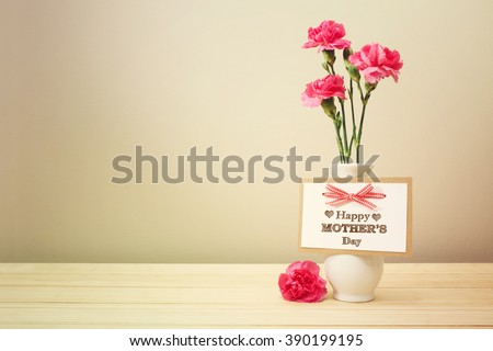 Mothers day message with pink carnations in a white vase