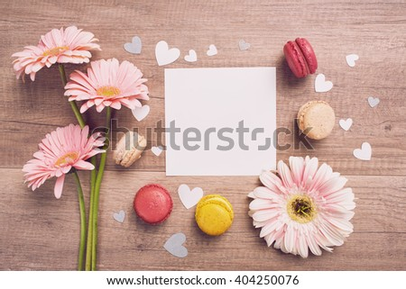 Mothers Day message with pink flowers and multi colored macarons on wooden table