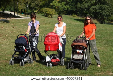 Mothers pushing their prams through the park in summer