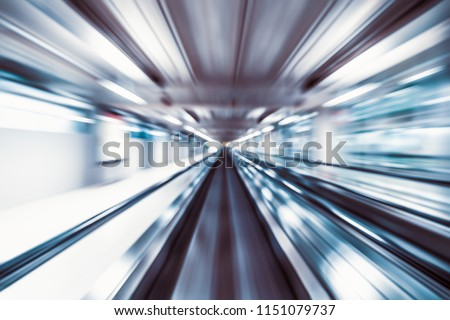 Motion blur abstract background, fast moving walkway or travelator in airport terminal transit, zoom effect, center diminishing perspective. Transportation, warp speed, or business technology concept
