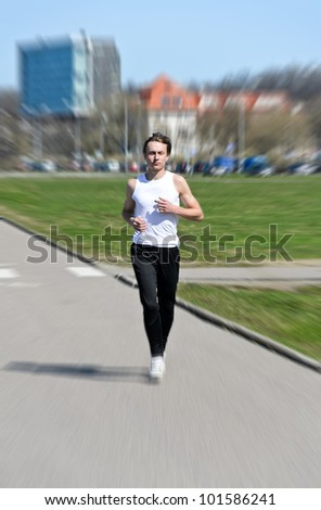 Motion Blur: Athletic young male running - stock photo