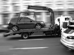 Motion blur, car tow truck rides on a city street