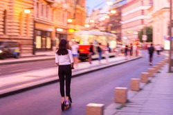 Motion blur effect. Girl riding electric step scooter in city center of Prague. People riding electric scooter at night. Photo with motion blur effect in Prague, Czech Republic.